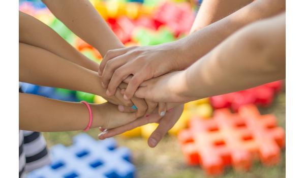 zeven kinderhanden in de lucht op elkaar gestapeld