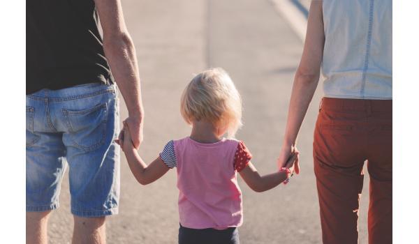 Jong kind hand in hand tussen twee volwassenen in